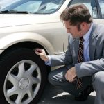 Car owner inspecting his flat front tire for a screw