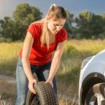 Young woman rolling spare tire to change the flat one