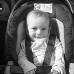 Black and white image of happy smiling baby boy posing in child safety car seat